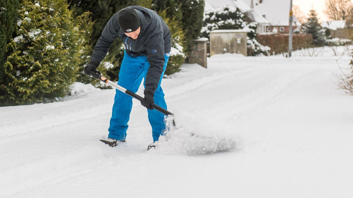 Mann schippt auf der Straße Schnee