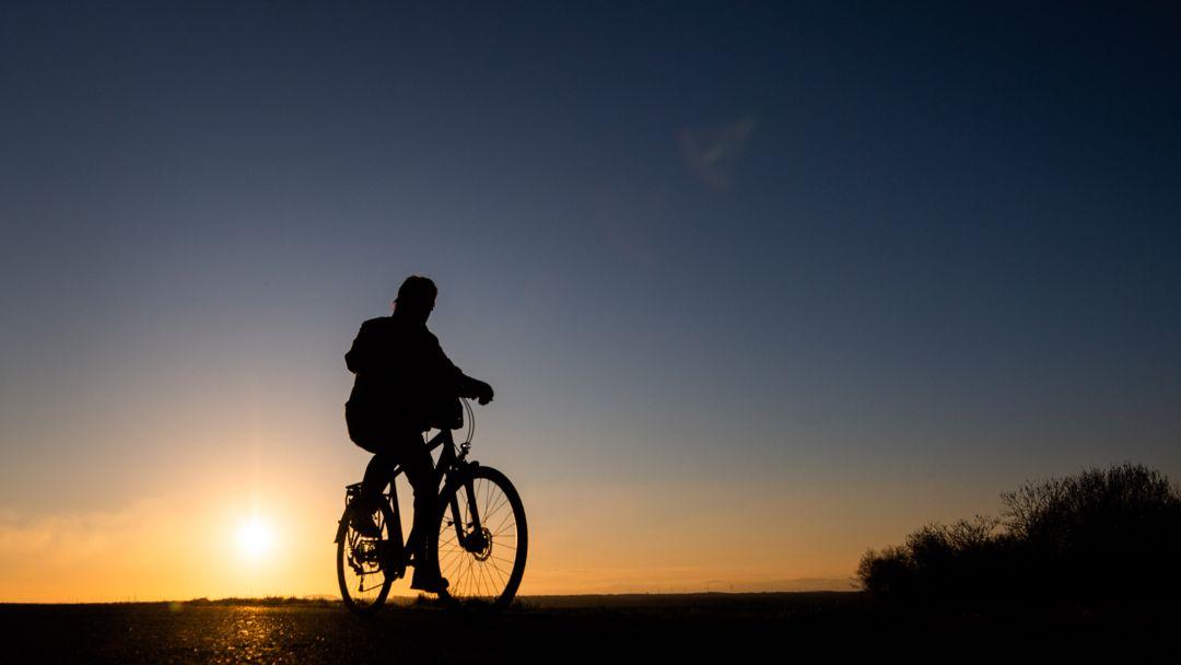Ein Mann fährt mit einem Fahrrad bei Sonnenaufgang über einen Feldweg (Symboldbild)