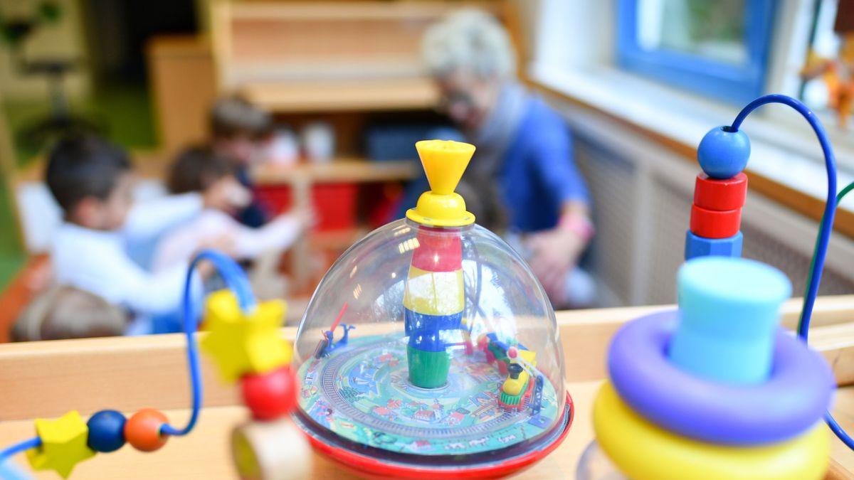 Eine Erzieherin spielt in einer Kita mit Kindern. Im Vordergrund steht Spielzeug.