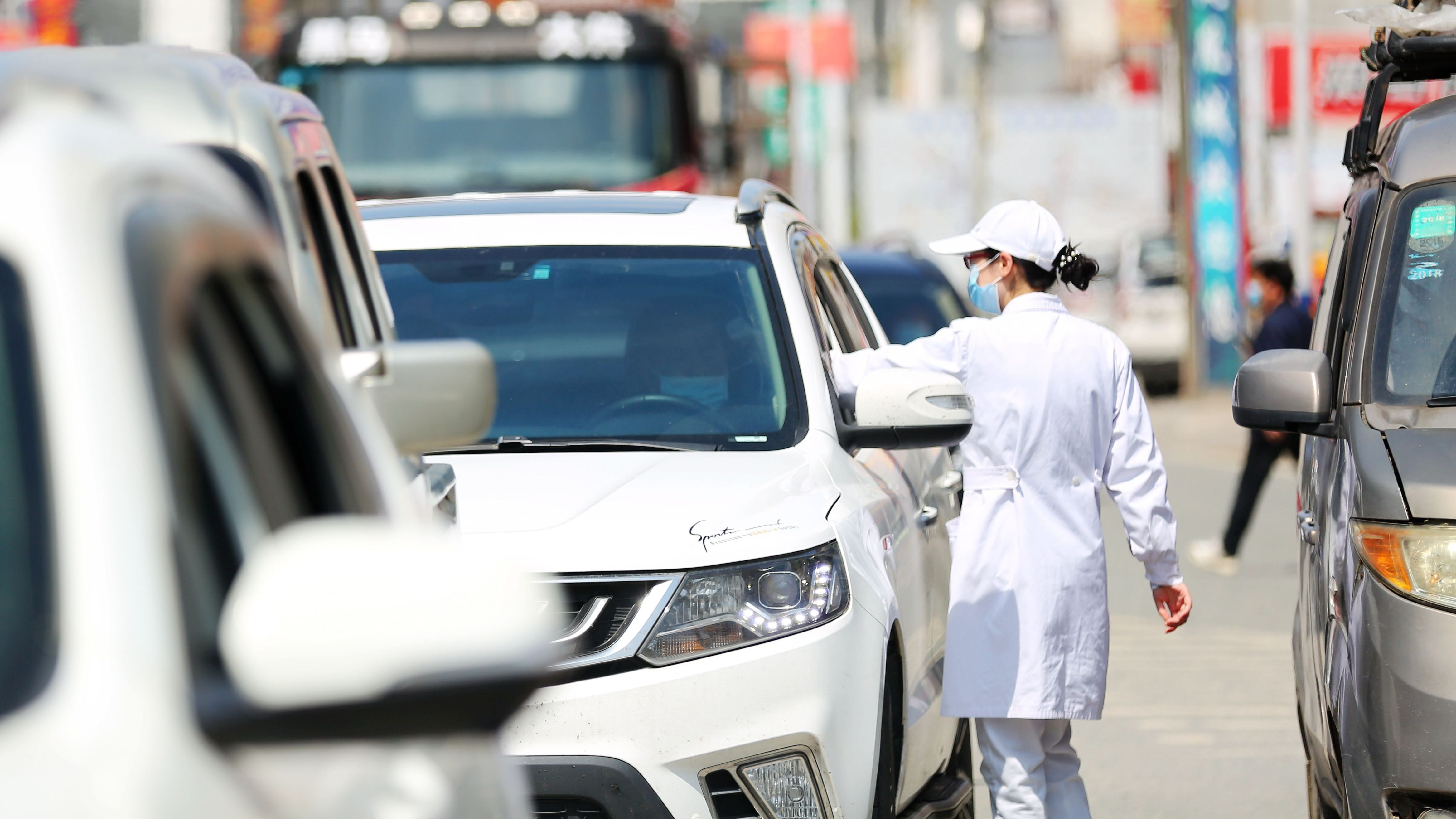 Weiß gekleidete Beamtin hält in Wuhan Autos an und misst Fieber