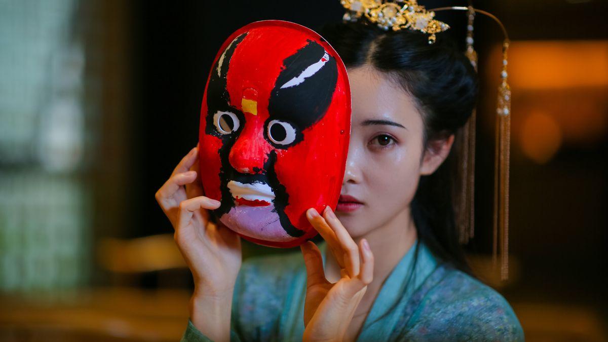 Junge Frau hält eine rot-schwarze Maske halb vor ihr Gesicht