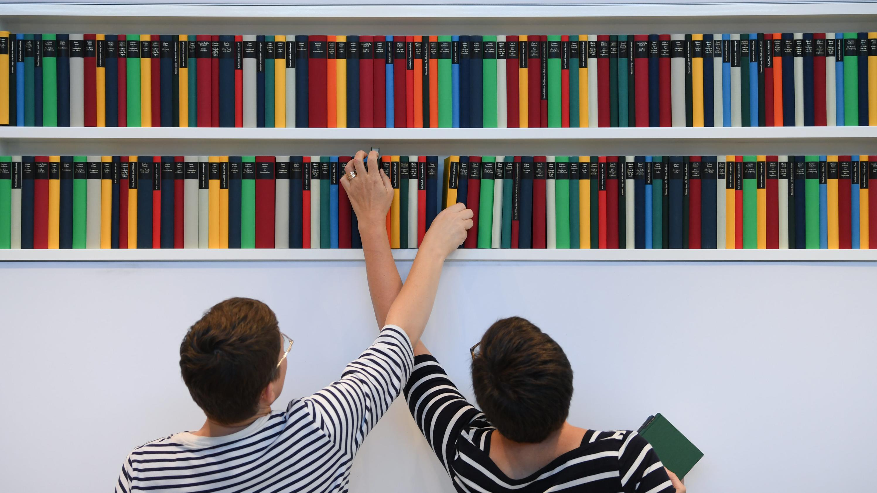 Zwei Frauen greifen nach Büchern in einem Bücherregal