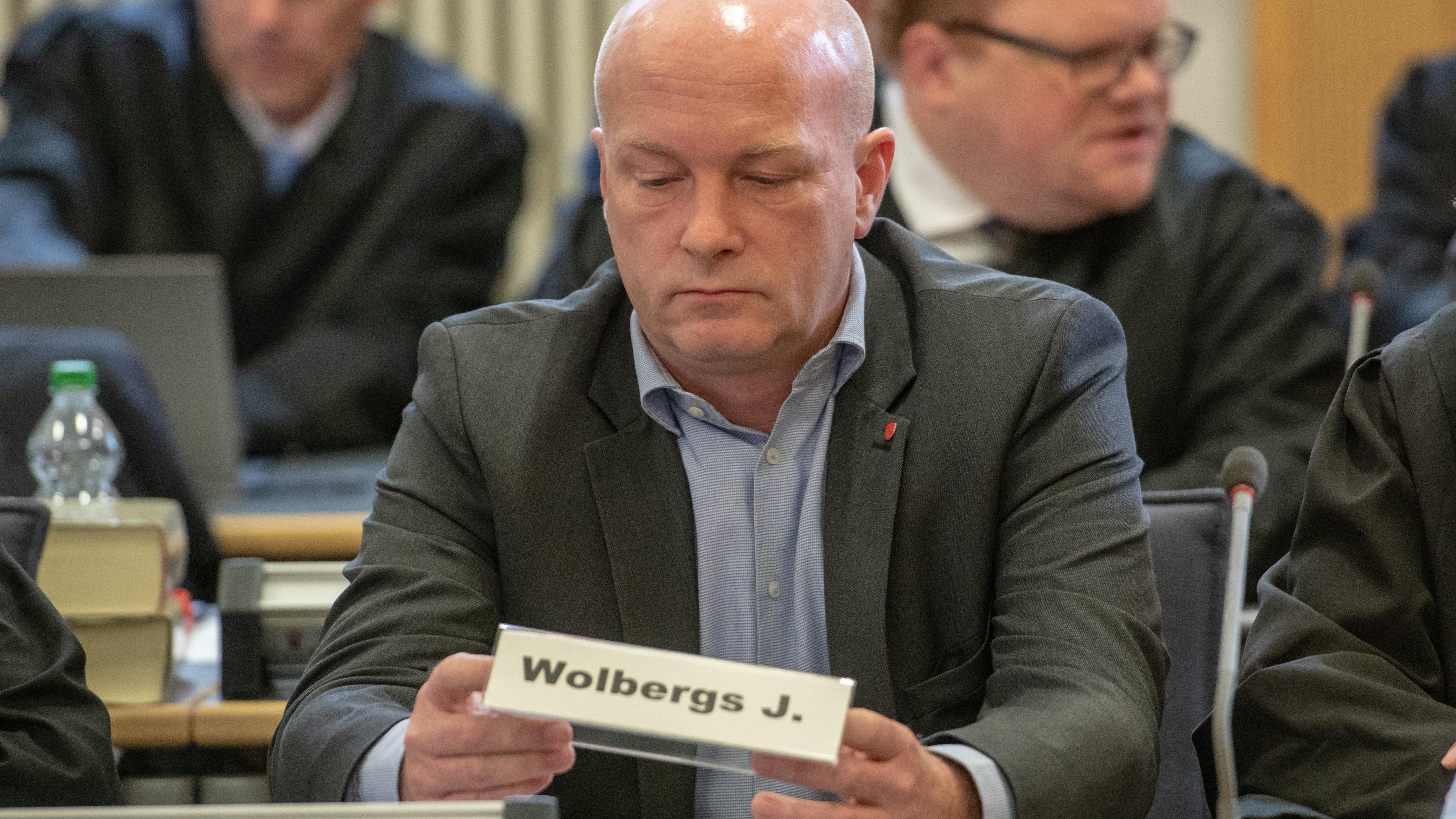 Joachim Wolbergs hält im Landgericht Regensburg sein Namensschild in Händen