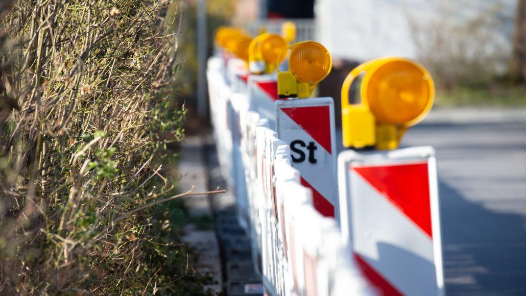 Eine Baustelle ist mit rot-weißen Verkehrsbaken abgesperrt, auf denen gelbe Blinklichter montiert sind