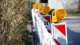 Eine Baustelle ist mit rot-weißen Verkehrsbaken abgesperrt, auf denen gelbe Blinklichter montiert sind | Bild:BR/Markus Konvalin