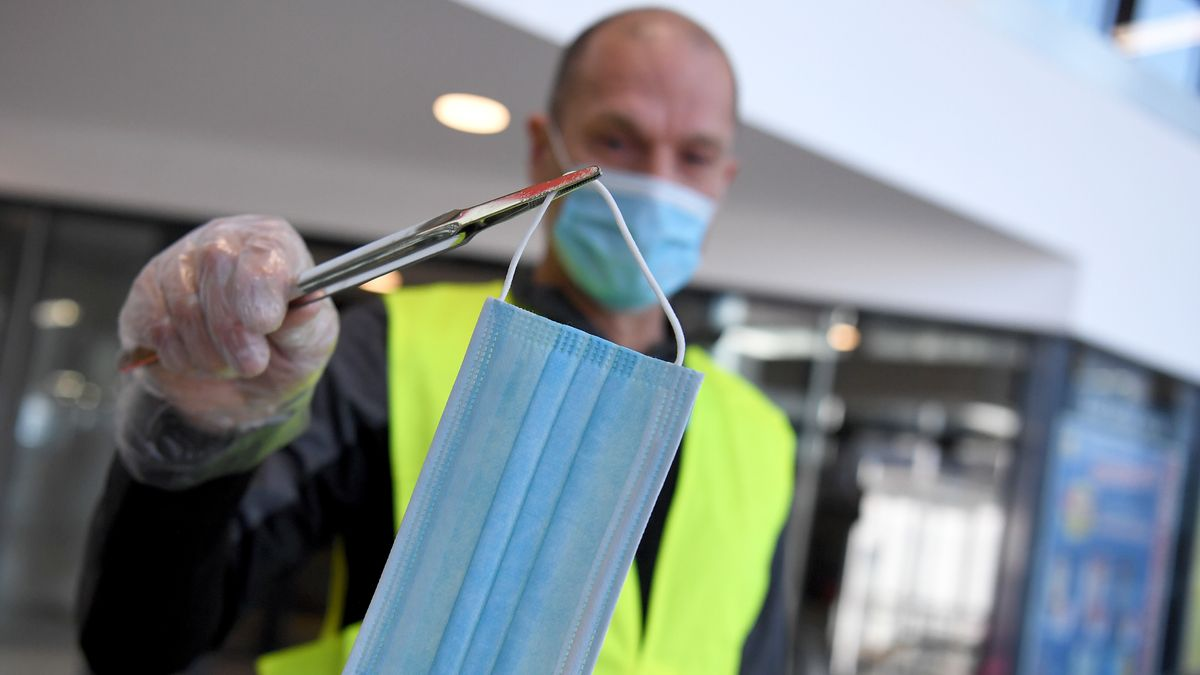 Ein Mitarbeiter eines Supermarktes in Österreich beim Aushändigen eines Mund- und Nasenschutzes