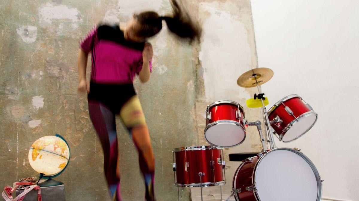 Eine bunte gekleidete Frau tanzt neben einem roten Drumset, die Aufnahme ist sehr unscharf