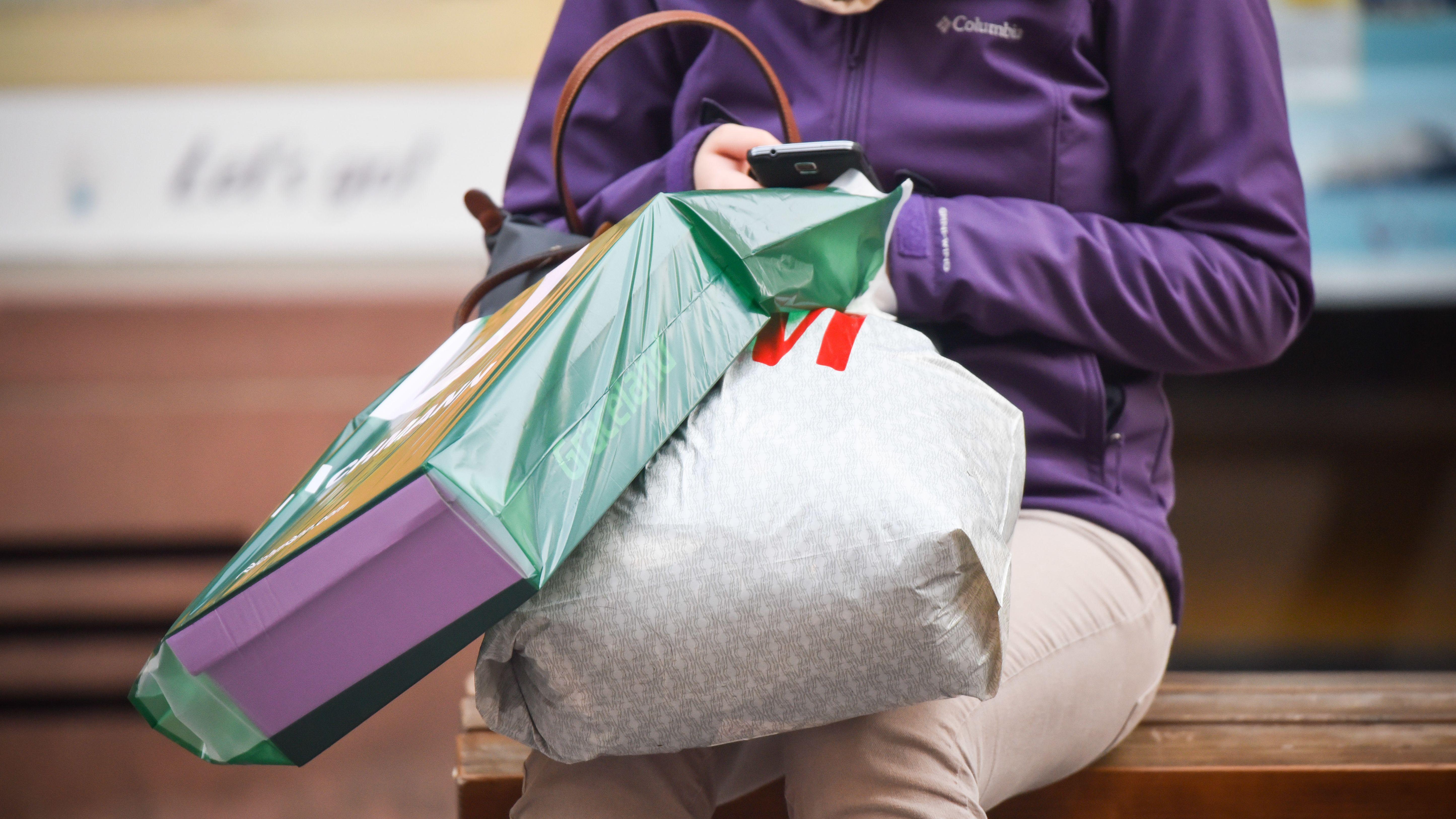 Frau mit Einkaufstaschen auf einer Bank