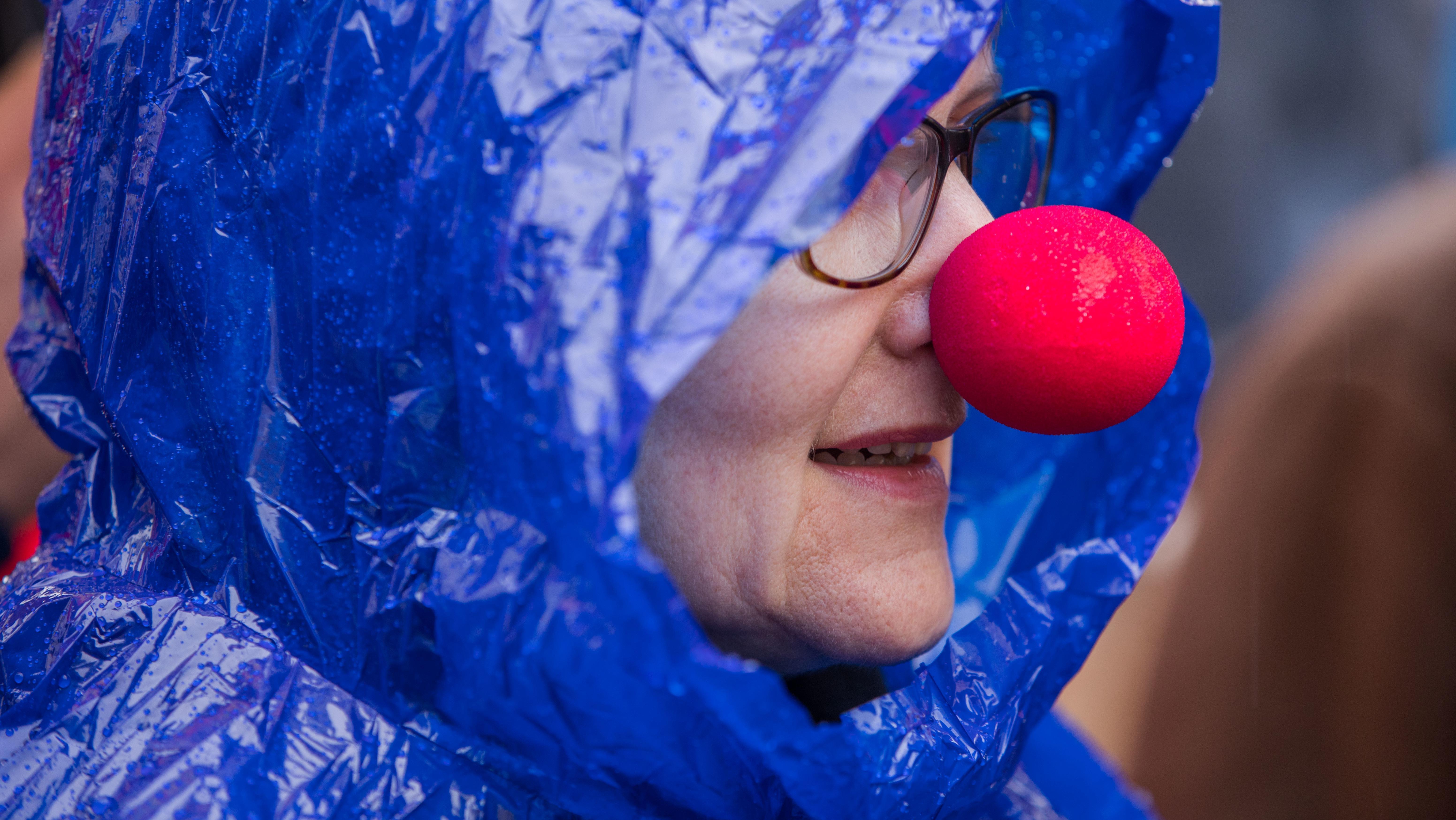 """Eine Besucherin mit """"roter Nase"""" beobachtet unter einem Regenmantel am in Schwerin (Mecklenburg-Vorpommern)"""