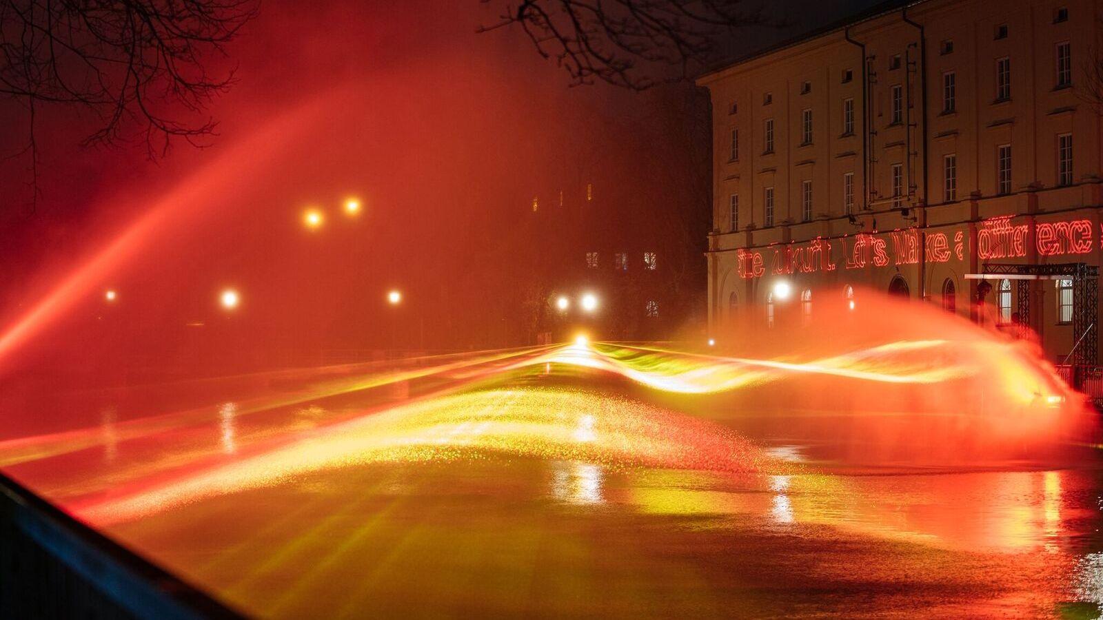 """Rote Lichtwellen über der Isar (Kunstaktion """"Burning River"""") an der Münchner Praterinsel"""