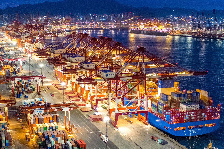 China Qingdao Containerschiffe liegen im nächtlich beleuchteten Containerterminal des Hafens von Qingdao