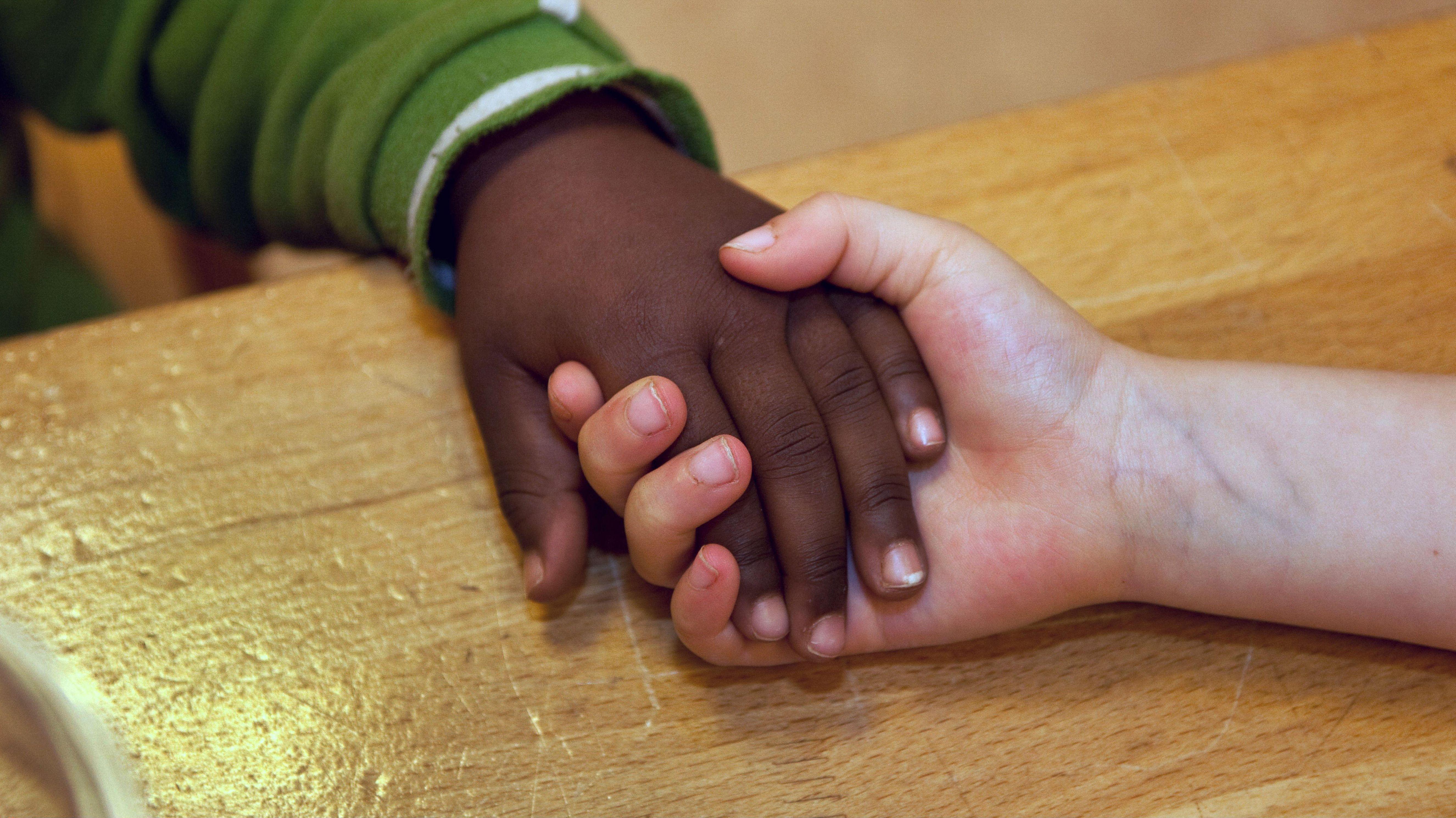 Hand eines dunkelhäutigen Kindes in der Hand eines hellhäutigen Betreuers (Symbolbild)