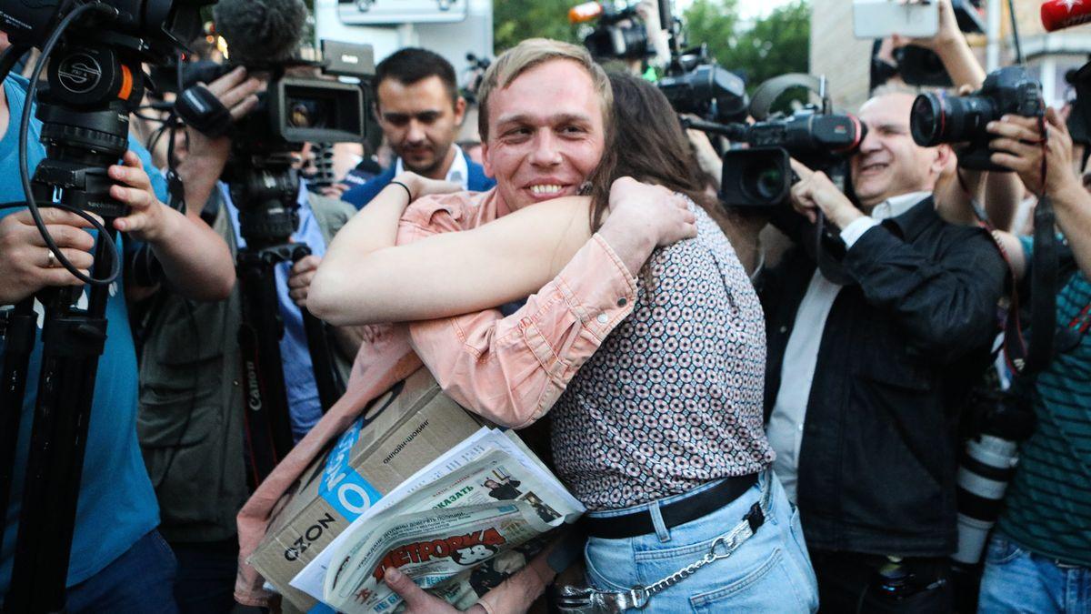 Der Journalist Iwan Godunow wird nach Einstellung der Ermittlungen gegen ihn von einer Unterstützerin umarmt, die Szene wird von zahlreichen Medienvertretern festgehalten.
