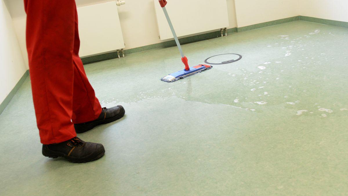 Ein Putzmann, von dem man nur die Beine und die Füße in Arbeitsschuhen sieht, wischt einen Fußboden mit Lauge