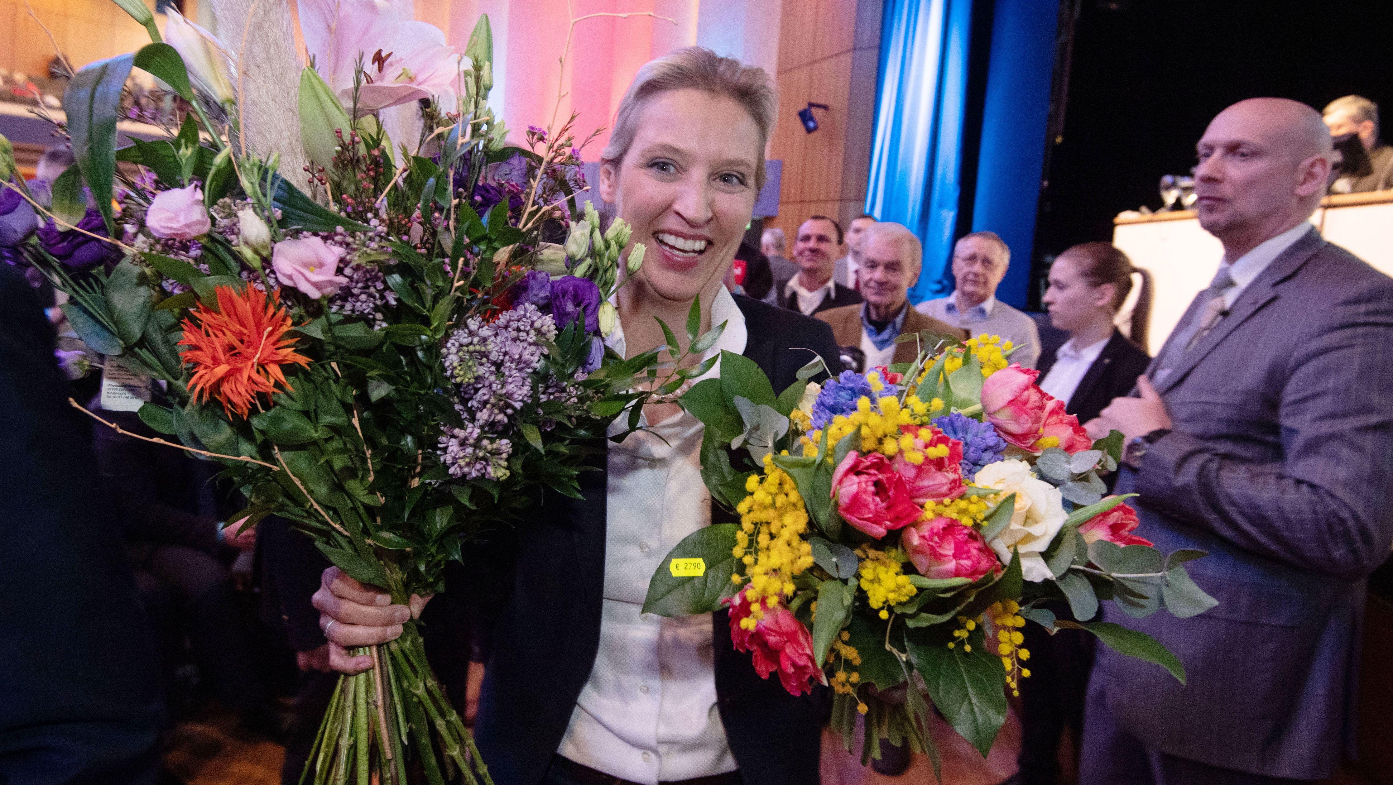 Alice Weidel, AfD-Fraktionsvorsitzende im Bundestag, hält beim AfD-Sonderparteitag nach ihrer Wahl zur Landesvorsitzenden der AfD Baden-Württemberg zwei Blumensträuße in den Händen.