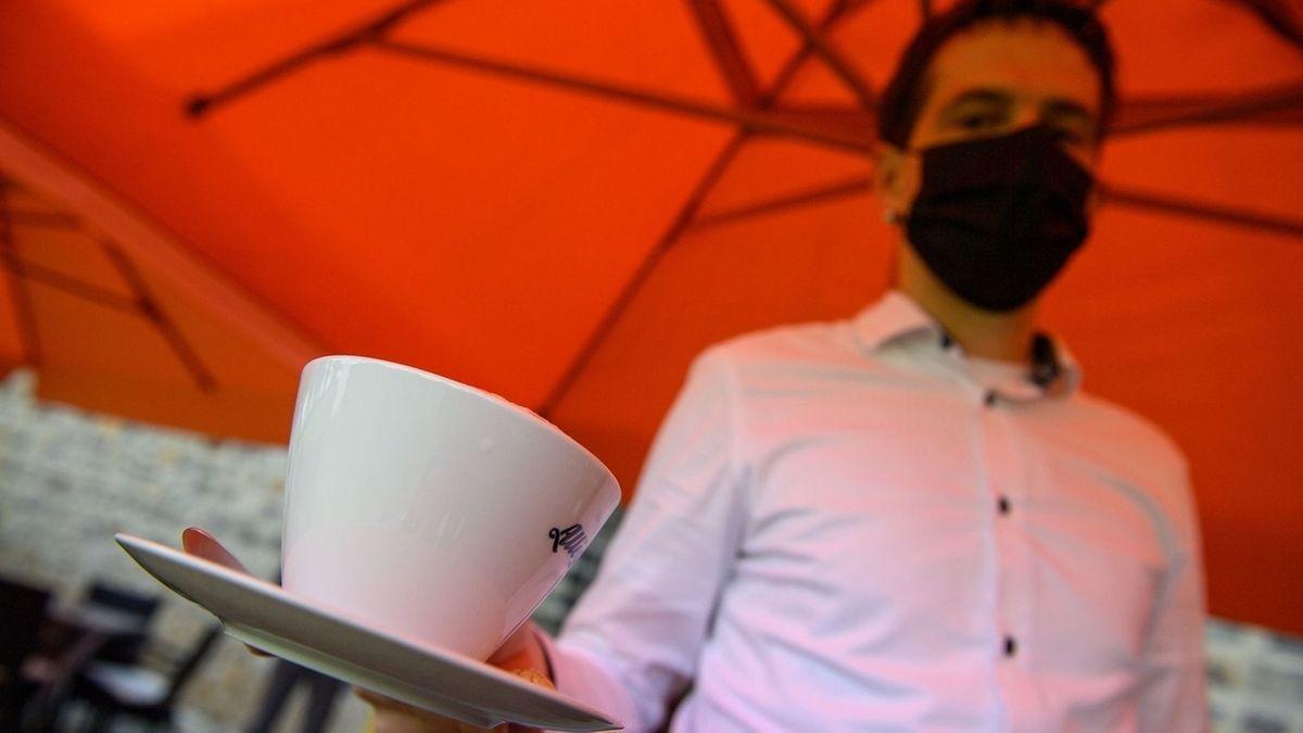Ein Mitarbeiter serviert Kaffee.