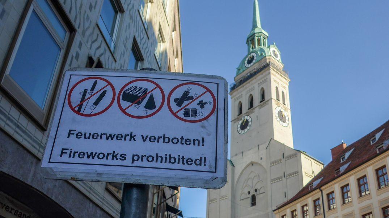 """Nahaufnahme eines Schildes mit der Aufschrift """"Feuerwerk verboten!"""" und drei Piktogrammen von verbotenen Feuerwerkskörpern. Im Hintergrund der Alte Peter in der Münchner Innenstadt im Sonnenschein."""