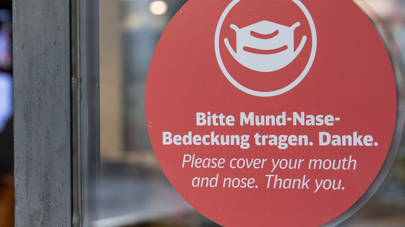 Der Hinweis zum Tragen eines Mund-und Nasenschutzes klebt auf einer Bahnhofstüre.