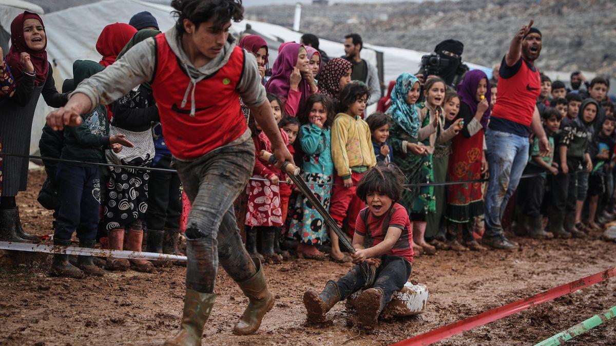 Syrische Kinder und Jugendliche bei einem Schlittenrennen im Schlamm