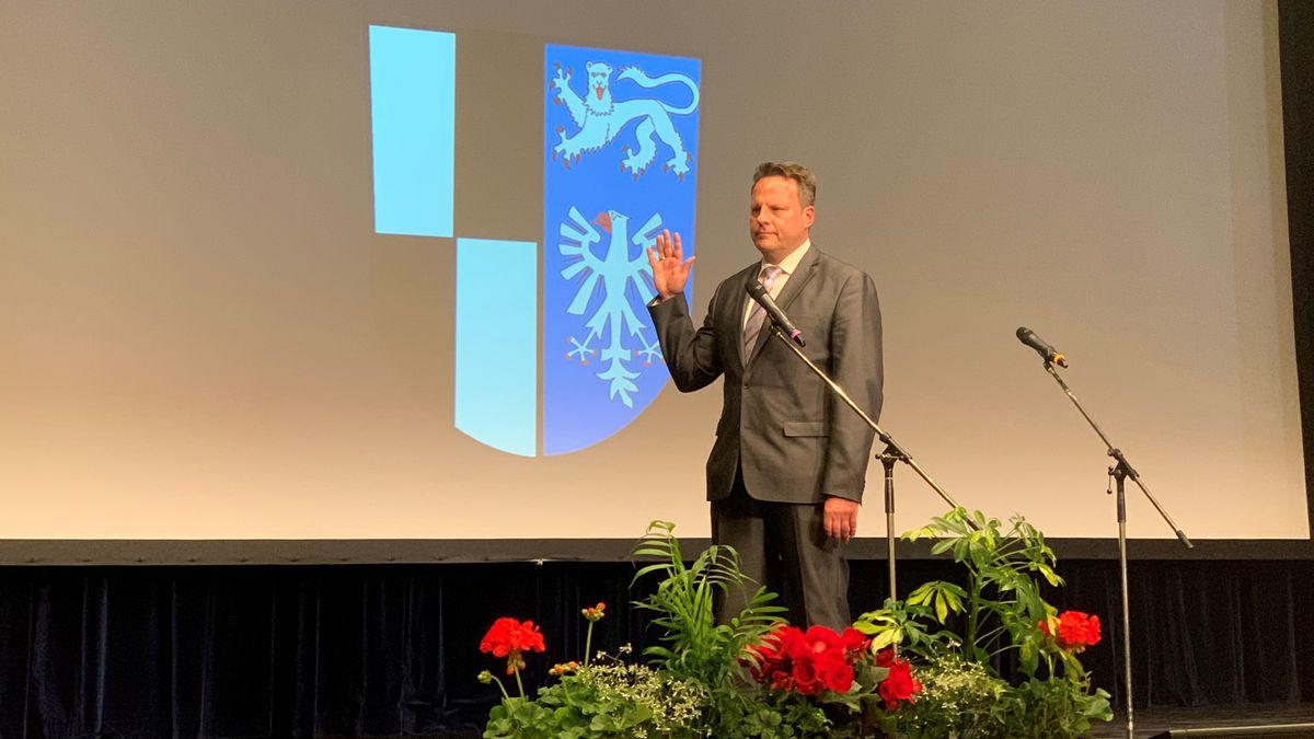 Ingo Lehmann steht auf der Bühne und hebt die Hand zur Vereidigung.