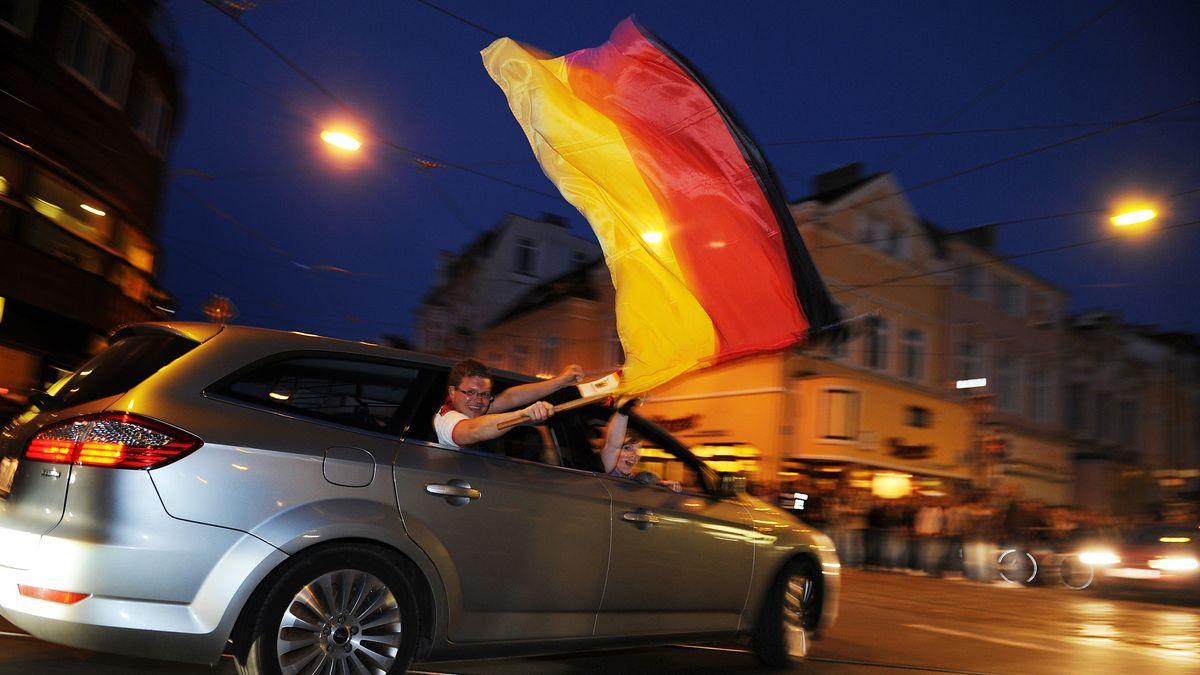 Deutschland-Fans fahren mit einem Auto durch eine Innenstadt. Ein Mann schwenkt eine Fahne.
