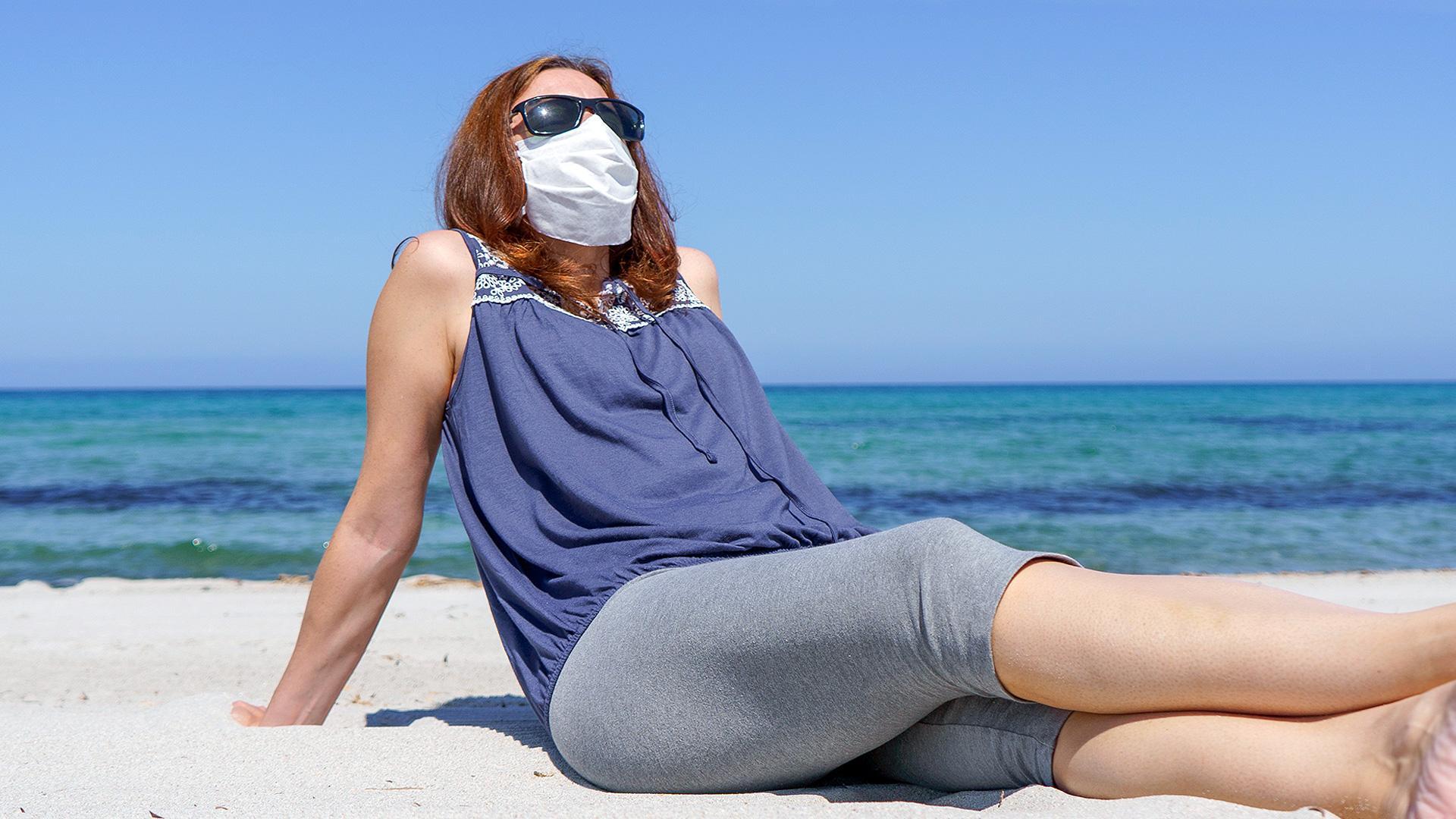 Frau sitzt mit Sonnenbrille und Gesichtsmaske am Strand