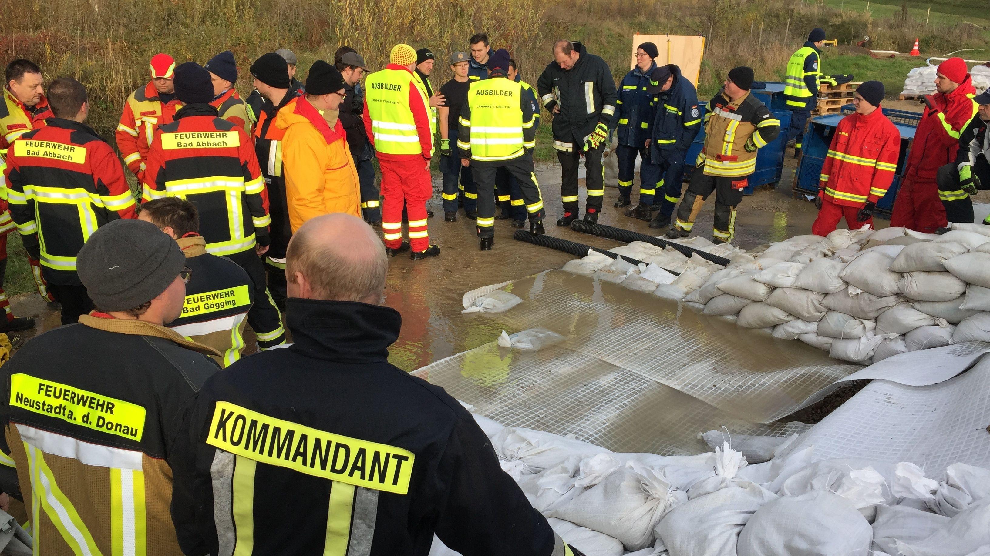 Einsatzkräfte proben das Auslegen von Sandsäcken am Übungsdeich