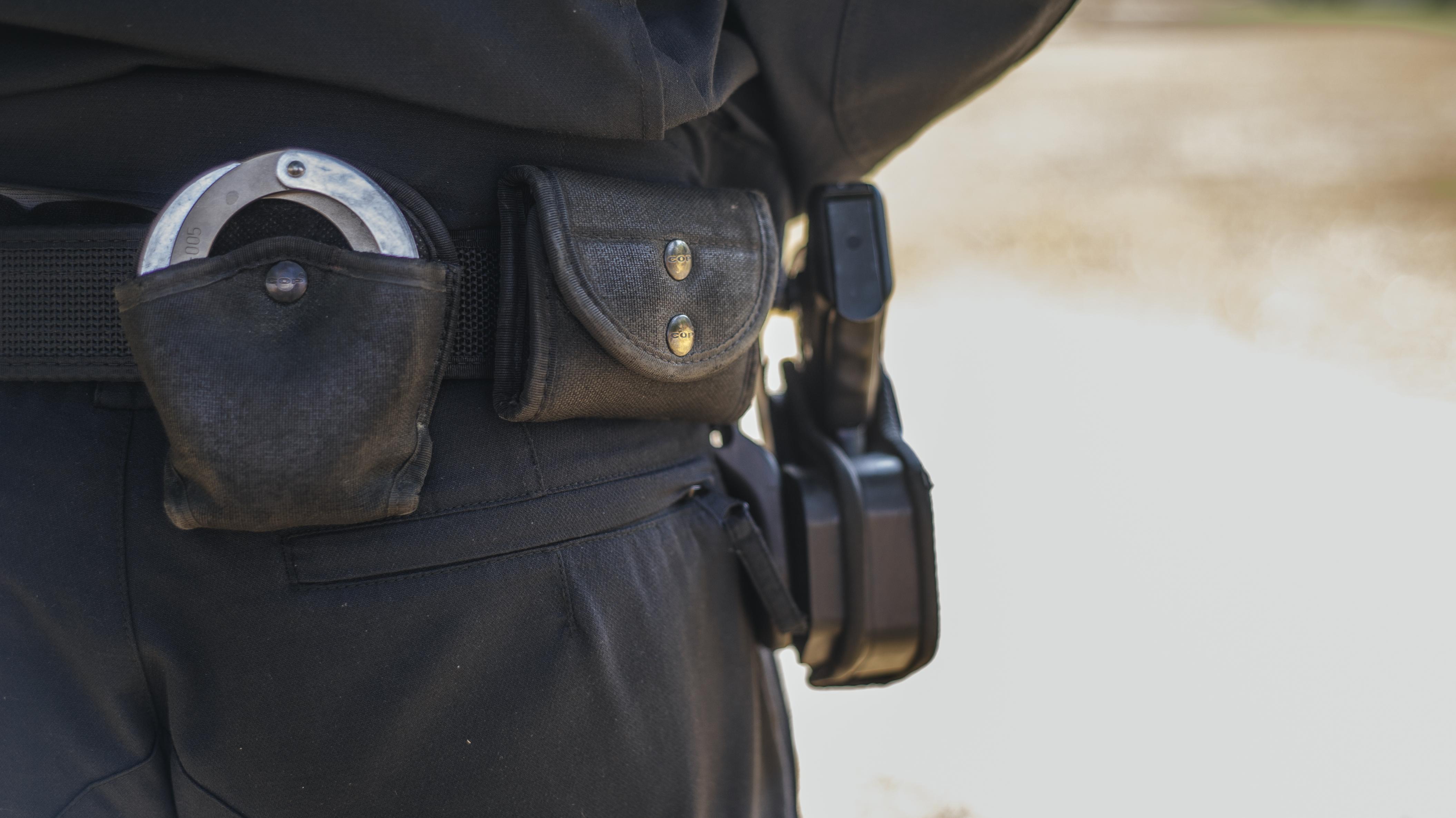 Polizist von hinten mit Dienstwaffe und Handschellen