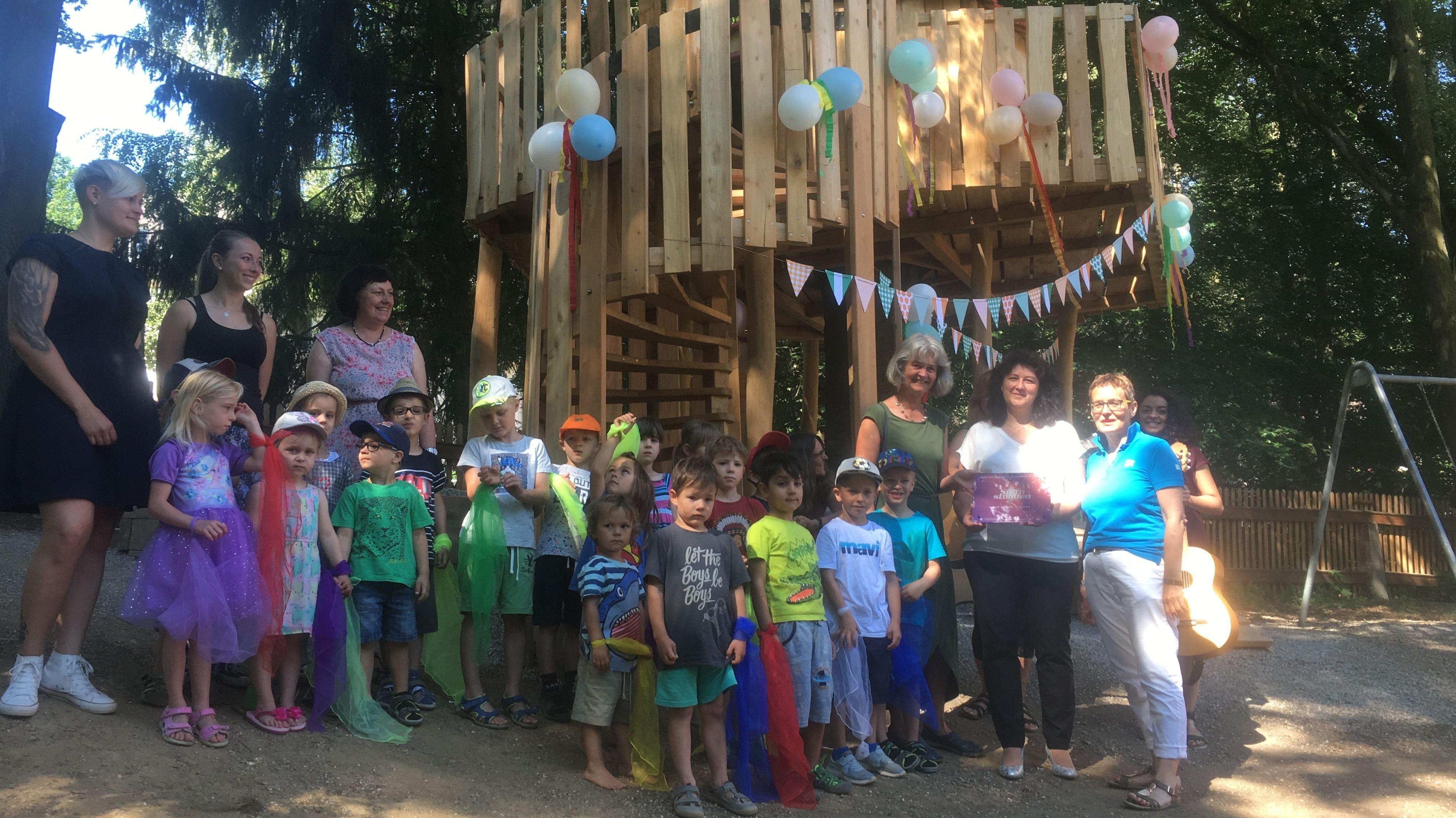 Kinder und ihre Betreuer stehen vor einem mit Luftballons geschmückten Baumhaus