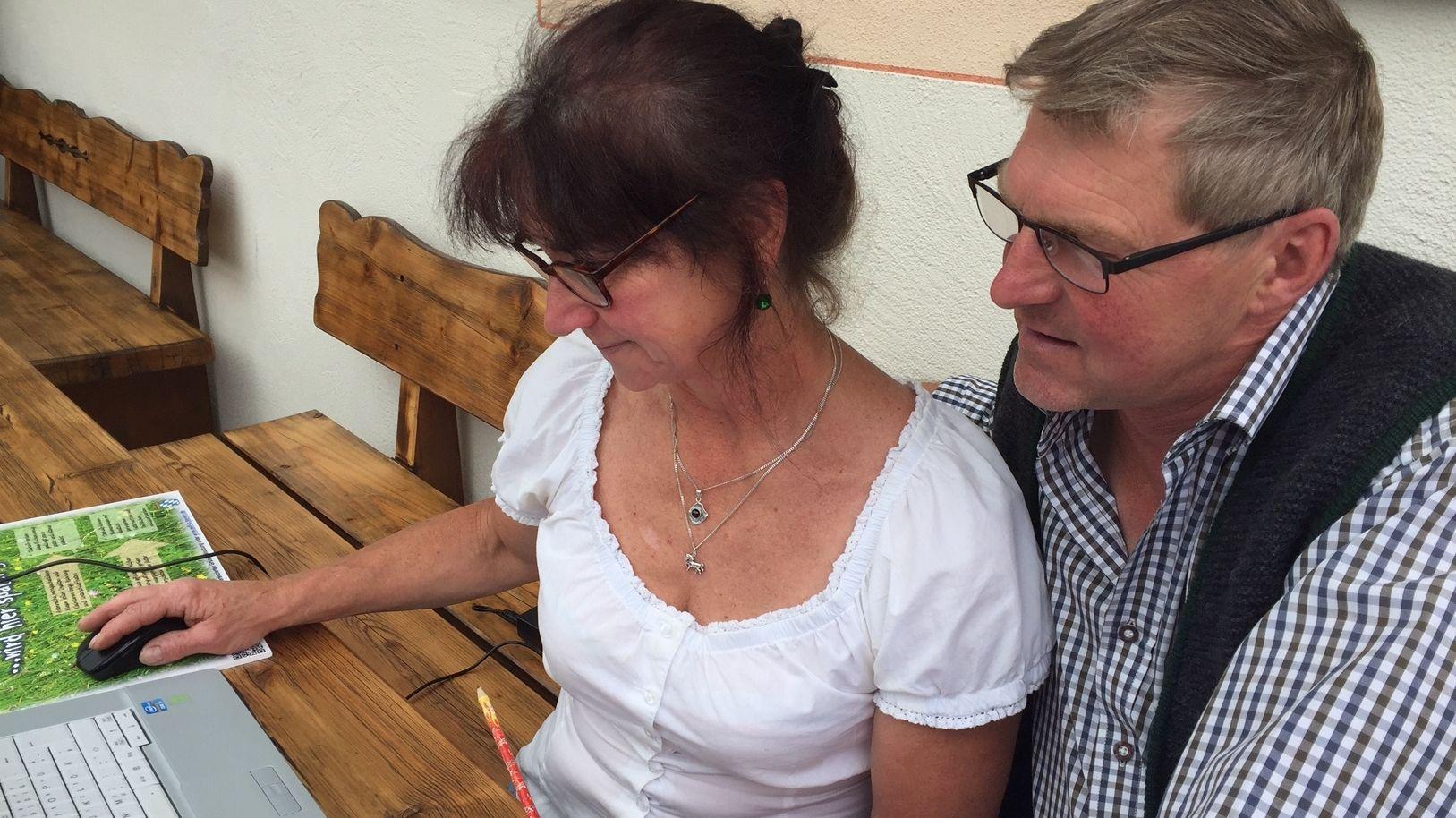 Babsi und Thomas Christophori sitzen am Tisch vor dem Haus und bearbeiten Buchungen am PC.