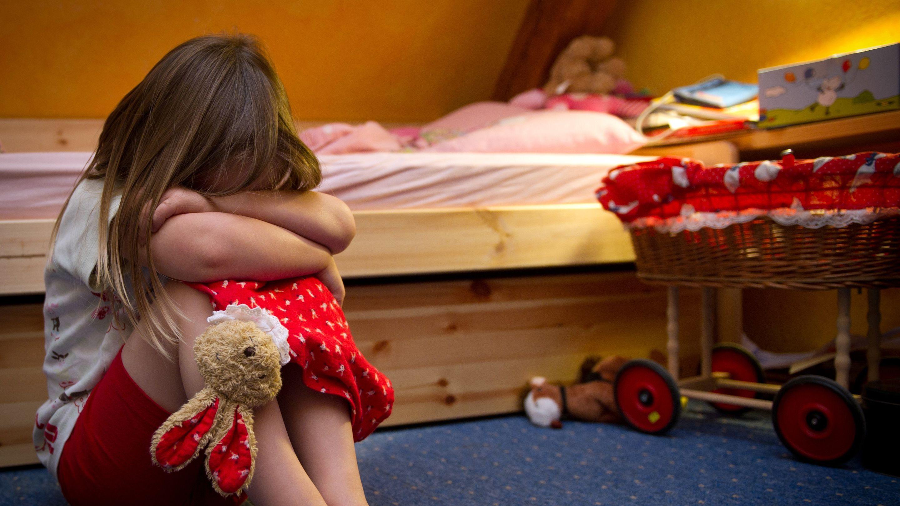 Mädchen sitzt weinend auf dem Boden