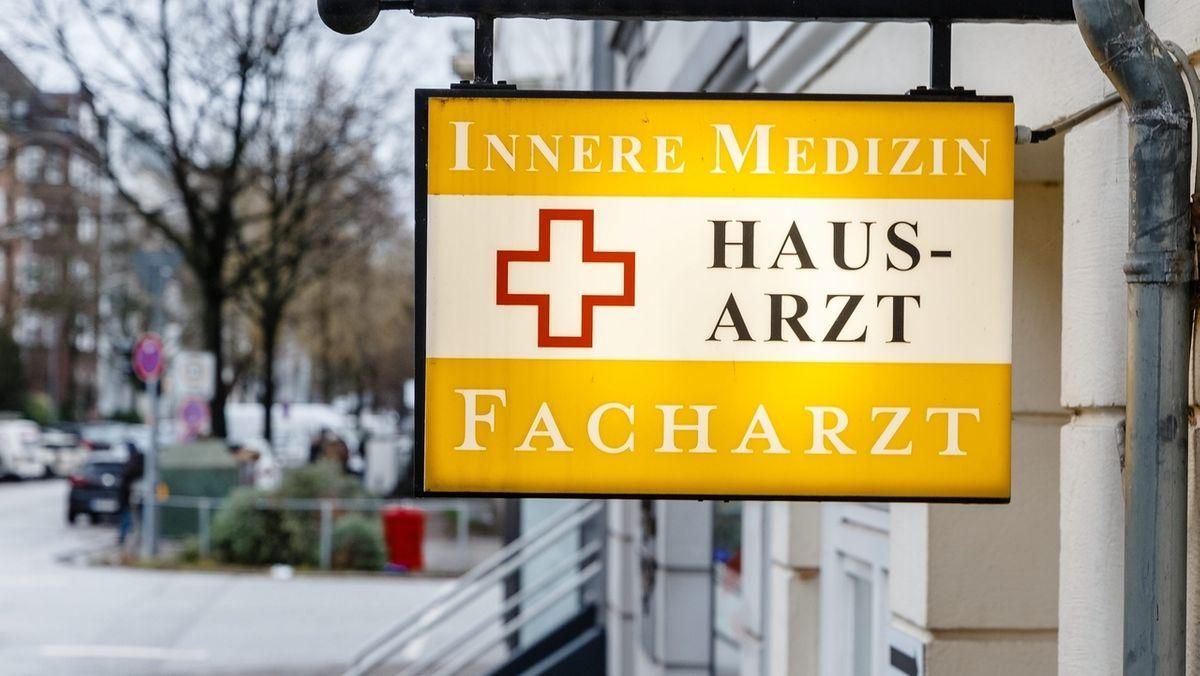 """Ein Schild mit der Aufschrift """" Innere Medizin, Hausarzt, Facharzt"""" hängt über der Eingangstür einer Arztpraxis."""