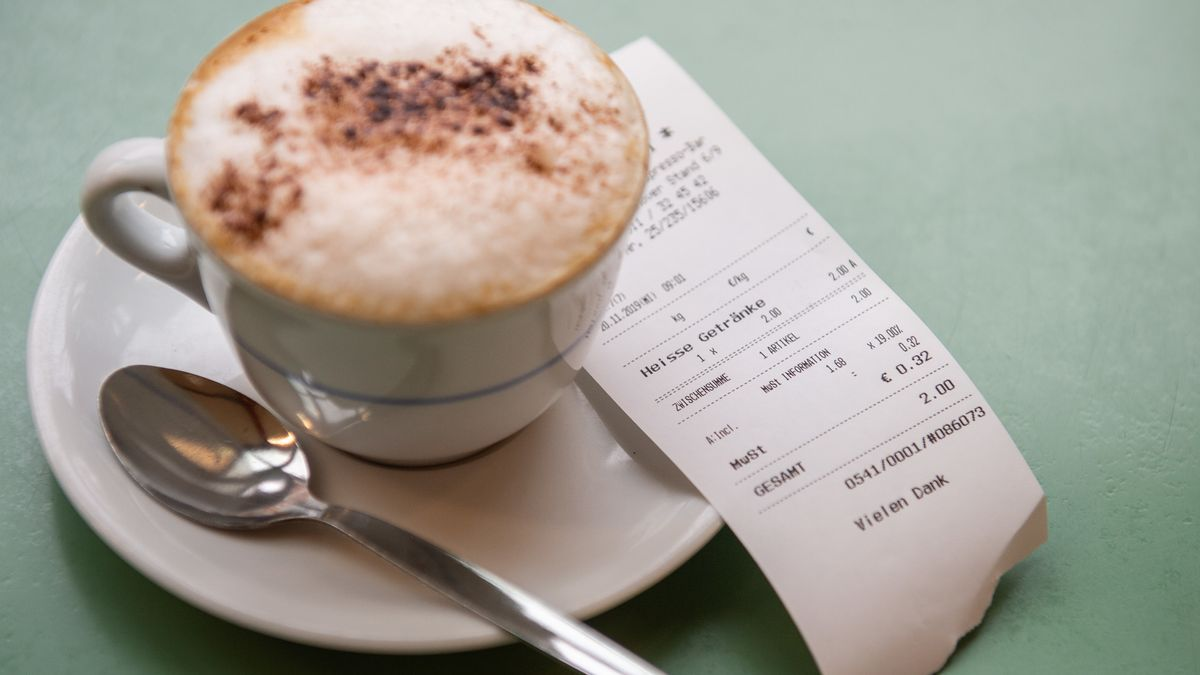 In einem Café liegt neben einer Tasse Cappuccino eine Quittung