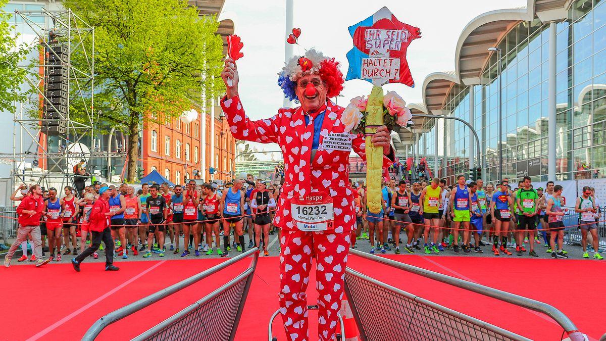 Michel Descombes  auf Stelzen im roten Clowns-Outfit.