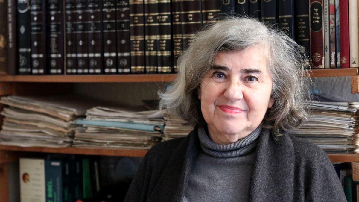 Eine ältere Frau mit grauen Haaren sitzt vor einer Bücherwand und blickt in die Kamera