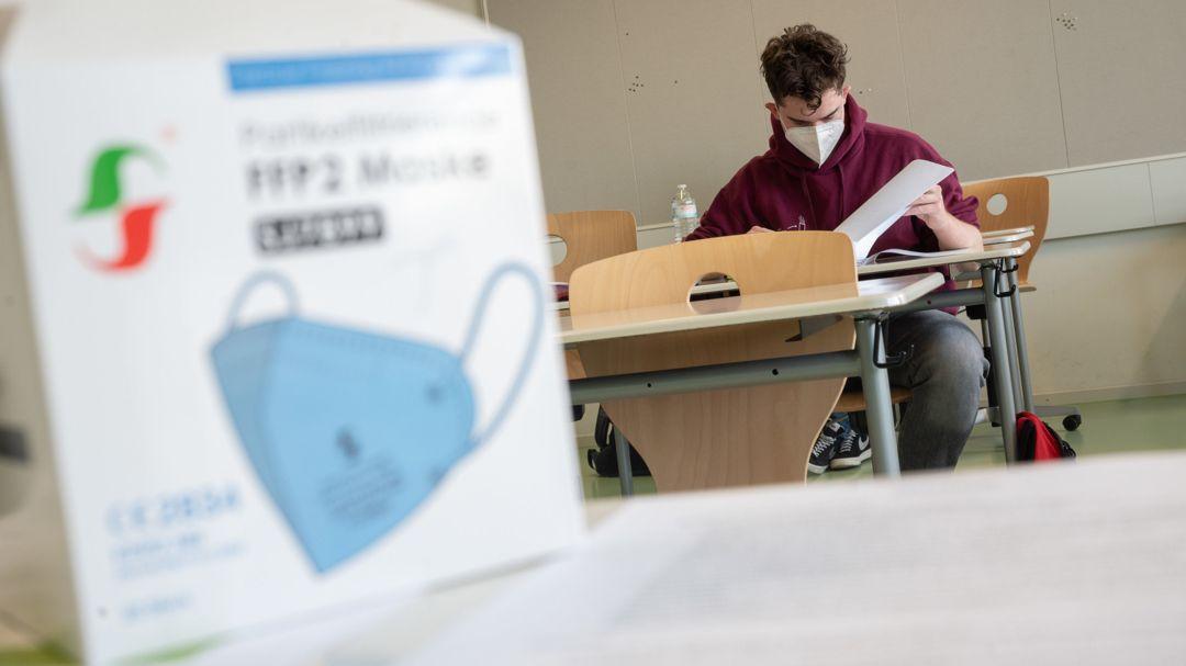 Ein Schüler mit medizinischer Maske sitzt in einem Klassenzimmer auf seinem Platz.