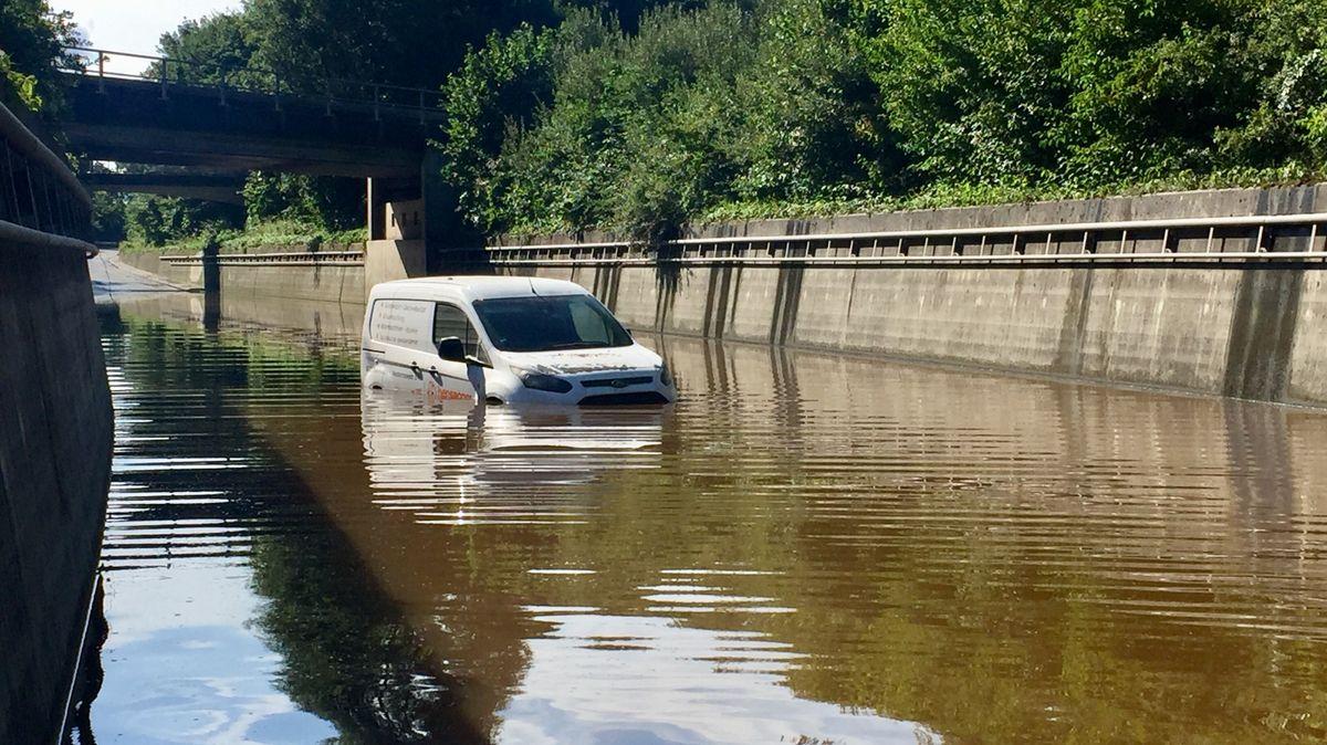 Auf der B15 bei Schechen steht ein Kleinbus bis zur Oberkante der Reifen im Wasser. Die Straße verläuft hier in einem betonierten Kanal, der am Dienstag komplett mit Wasser gefüllt war.