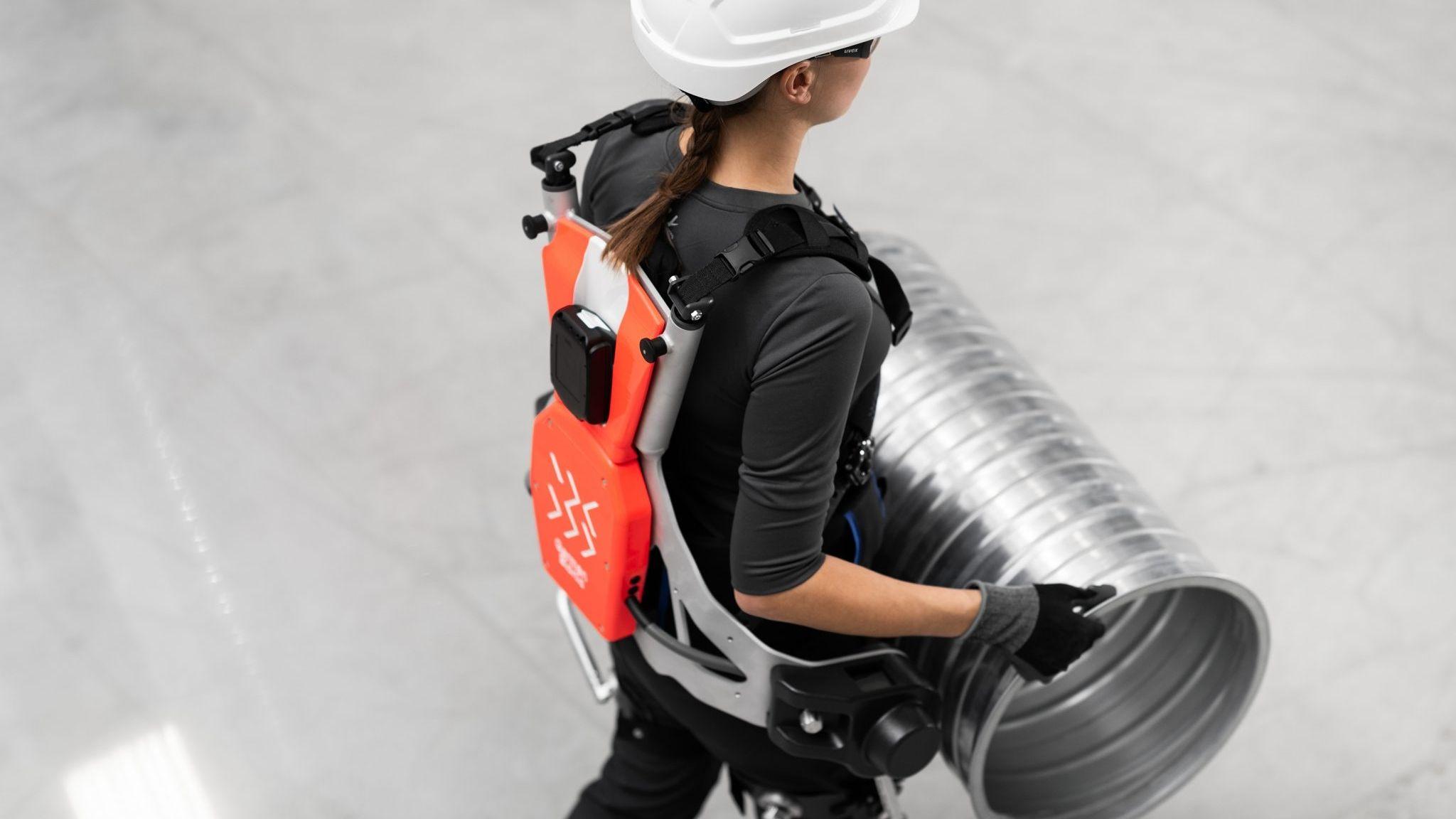 Arbeiterin nutzt ein Außenskelett als Tragehilfe für schwere Lasten