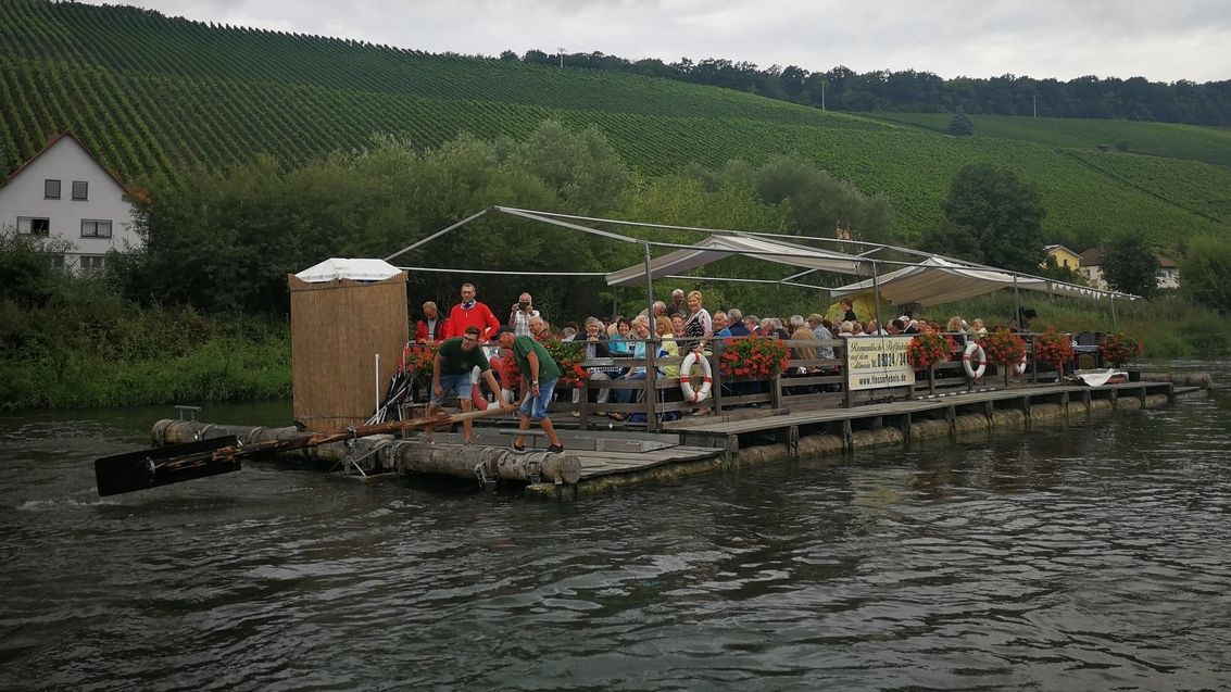 Eine Gruppe von Menschen fährt mit einem großen Floß auf dem Altmain.