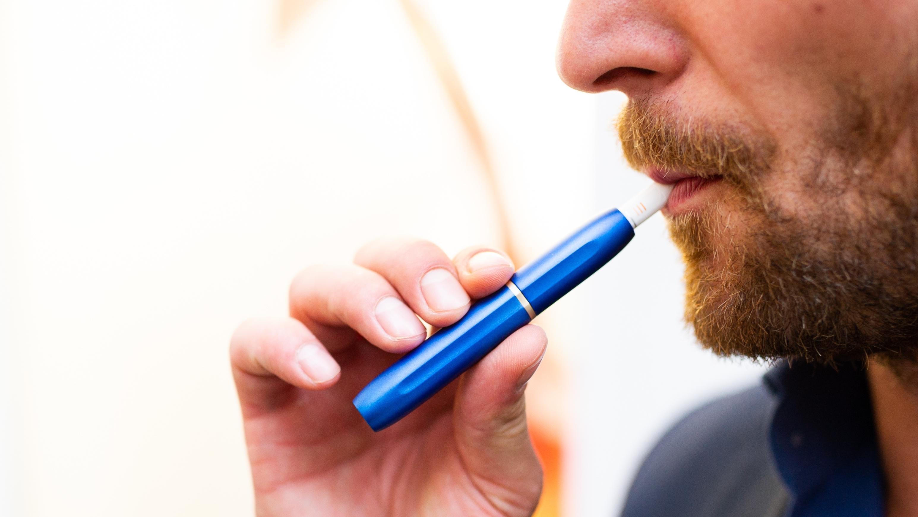 Ein Mann zieht an einem Tabakverdampfer. Tabakverdampfer wie IQOS oder Glo unterscheiden sich von E-Zigaretten.