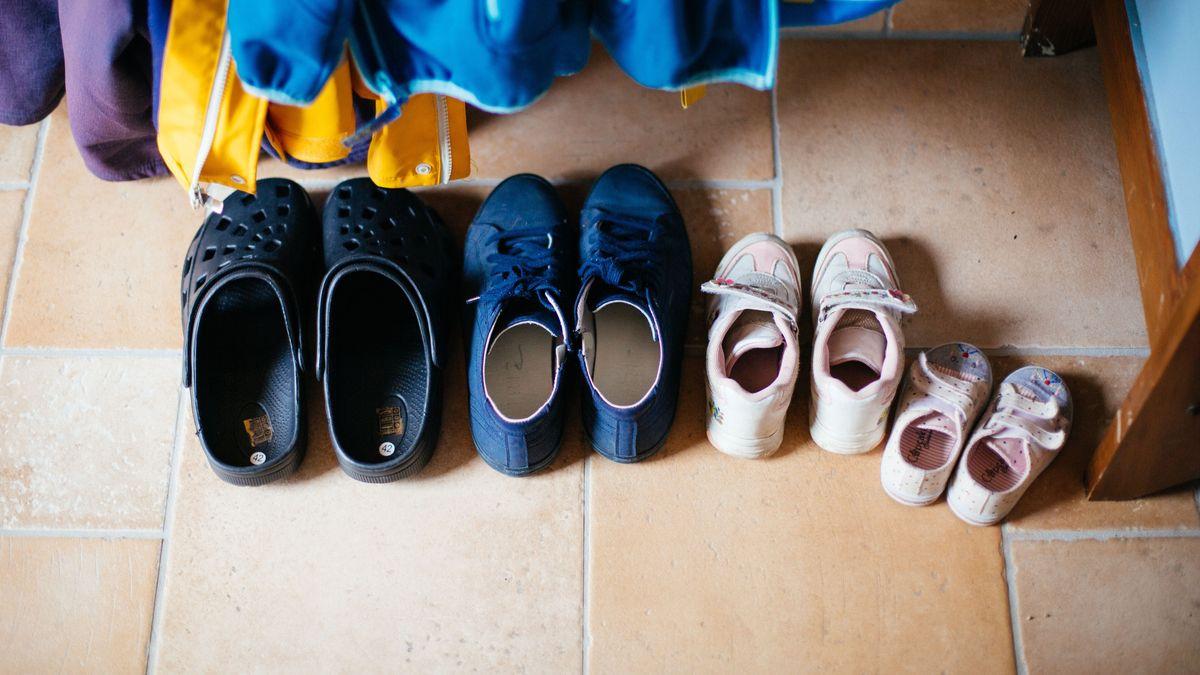 Vier Paar Schuhe stehen - stellvertretend für eine vierköpfige Familie - aufgereiht nach Größe nebeneinander.