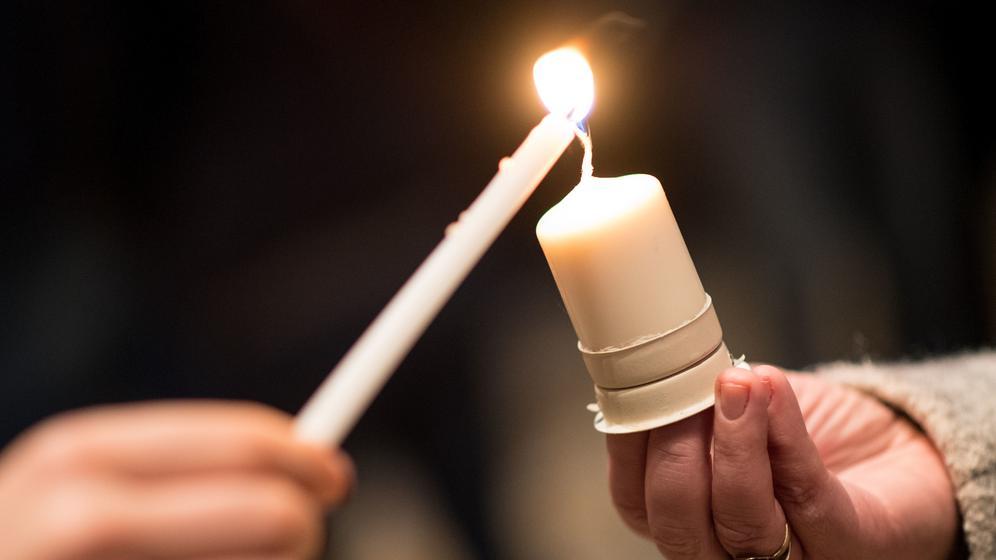 Eine Kerze wird an einer brennenden Kerze entzündet | Bild:picture alliance / Marius Becker/dpa