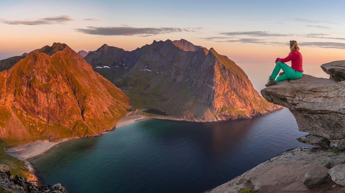 Eine Frau sitzt auf einem Felsen und blickt auf einen Fjord mit Bergen im Hintergrund.