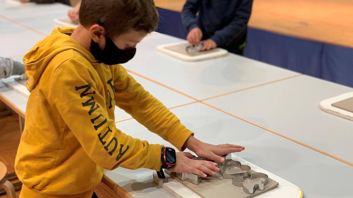 Ein Grundstschüler sticht Baumanhänger im Porzellanikon in Selb aus