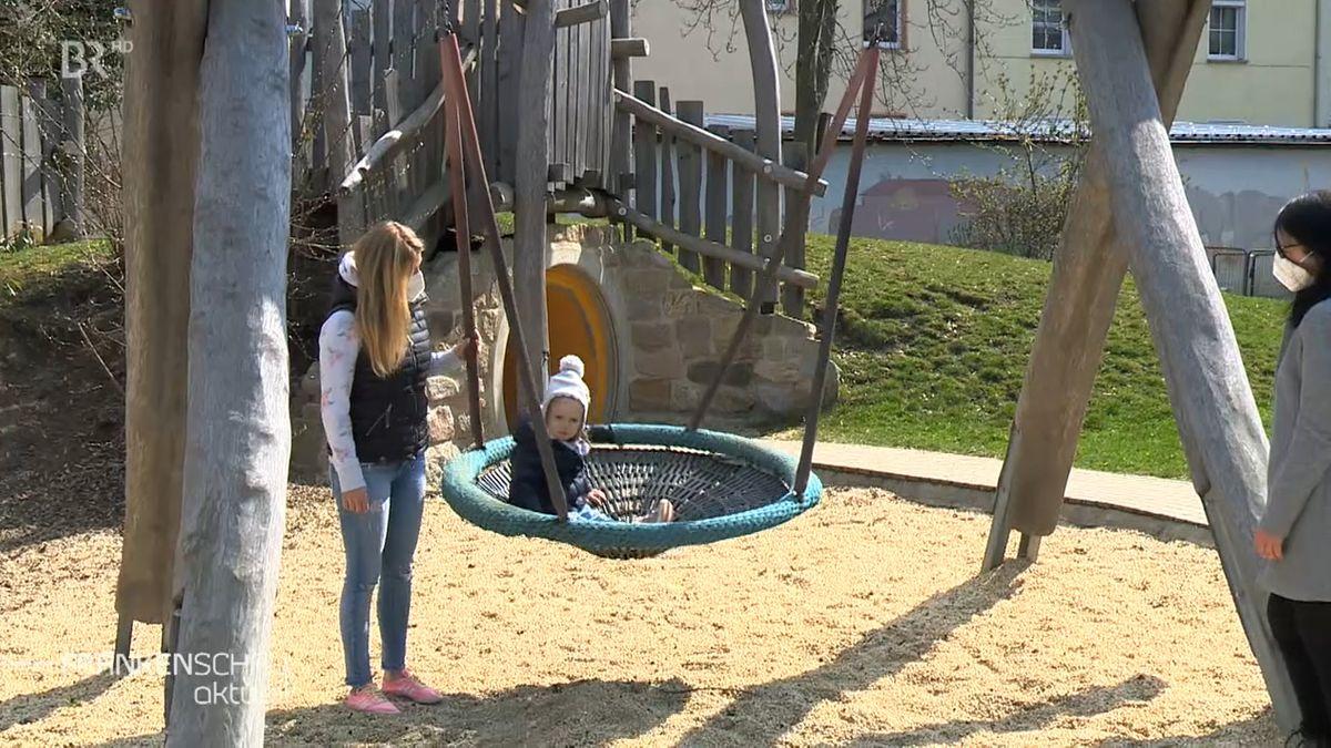 Auf einem Spielplatz sitzt ein kleines Kind in einer Schaukel