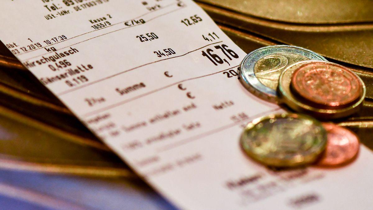 Wechelgeld liegt auf einem Kassenbon für ein Fleischgericht