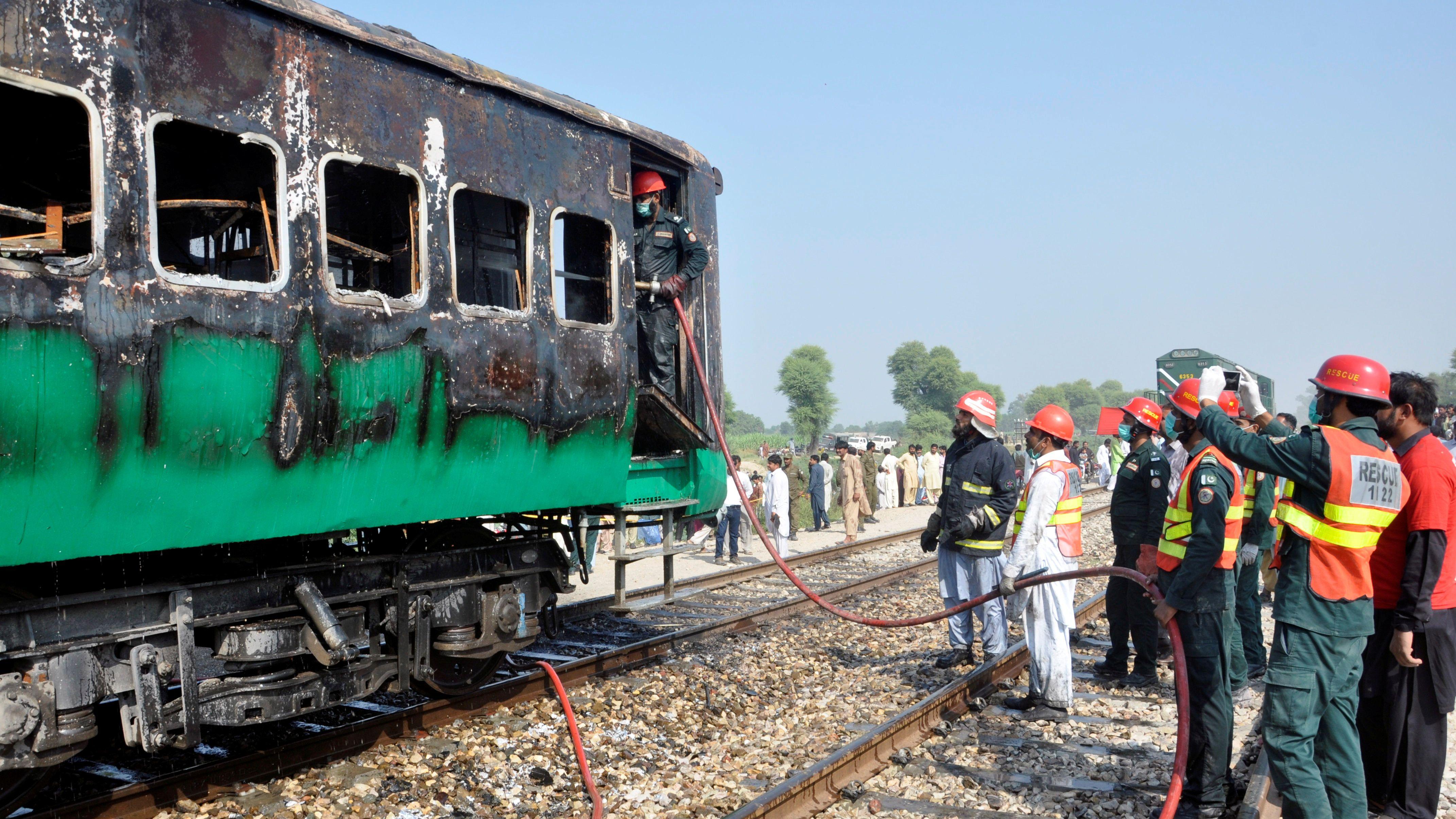 Feuerwehr und Rettungskräfte am ausgebrannten Zug in der Nähe der pakistanischen Stadt Rahim Yar Khan