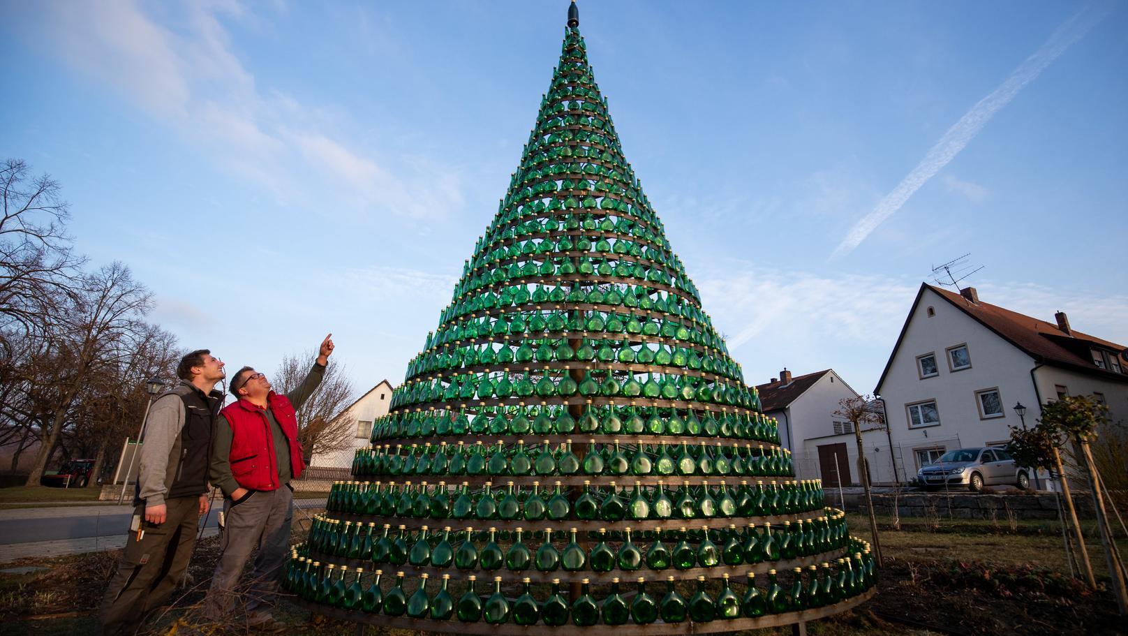 Nordheim Am Main: Guido Braun (r), Bürgermeister von Nordheim, und sein Sohn Nico stehen neben einem Weihnachtsbaum der aus 1099 Bocksbeutel-Flaschen besteht. Die Spitze des Baumes wird von einer grünen Jubiläumssektflasche geziert.