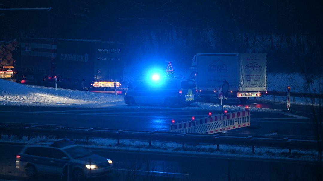 In der Dunkelheit steht ein Polizeiauto mit Blaulicht an einer Straße und hat eine Straßensperre für Kontrollen errichtet, dort stauen sich bereits Lastwagen.