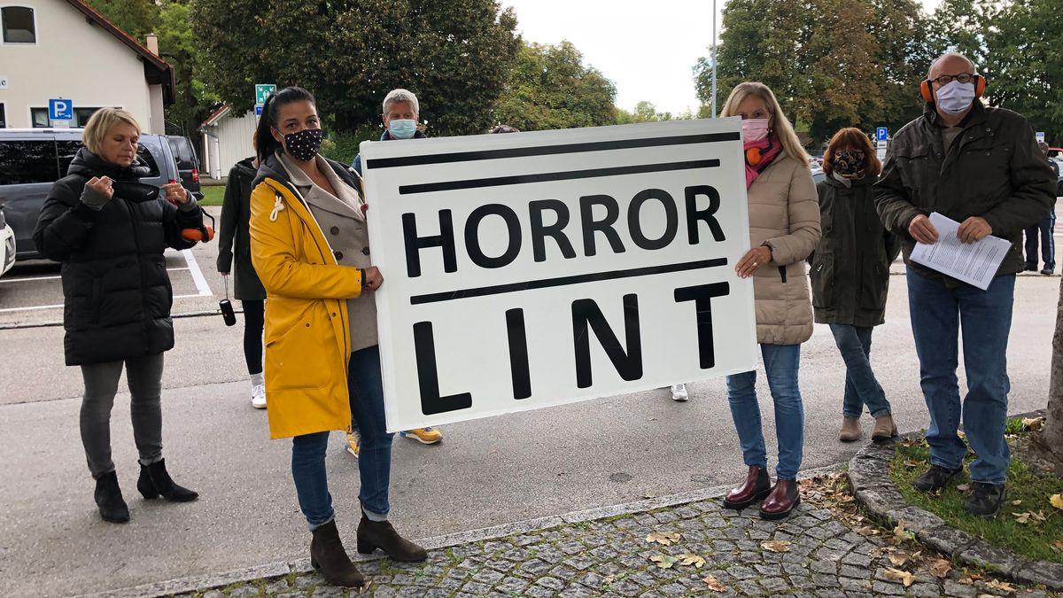 """Anwohner halten ein Plakat mit der Aufschrift """"Horror Lint"""" hoch."""